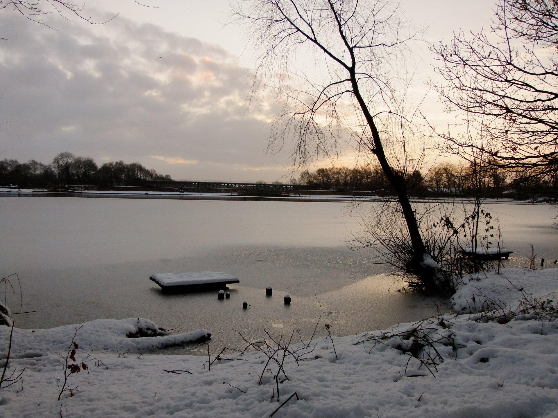 Fotografia wykonana zimą prezentuje duże jezioro oraz fragment jego brzegu okrytego śniegiem. Tafla jeziora jest okryta śniegiem ilodem. Przy samym brzegu nie ma lodu na jeziorze.