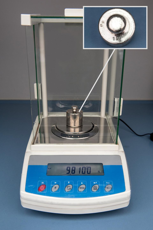 Fotografia wagi elektronicznej ustawionej na wyświetlanie wskazań wniutonach. Na szalce odważnik omasie 1 kg. Wyraźnie widać wyświetlacz wagi elektronicznej. Na wyświetlaczu widać wyraźnie wartość oraz jednostkę (N). Wyświetlana wartość to 9,81 N.