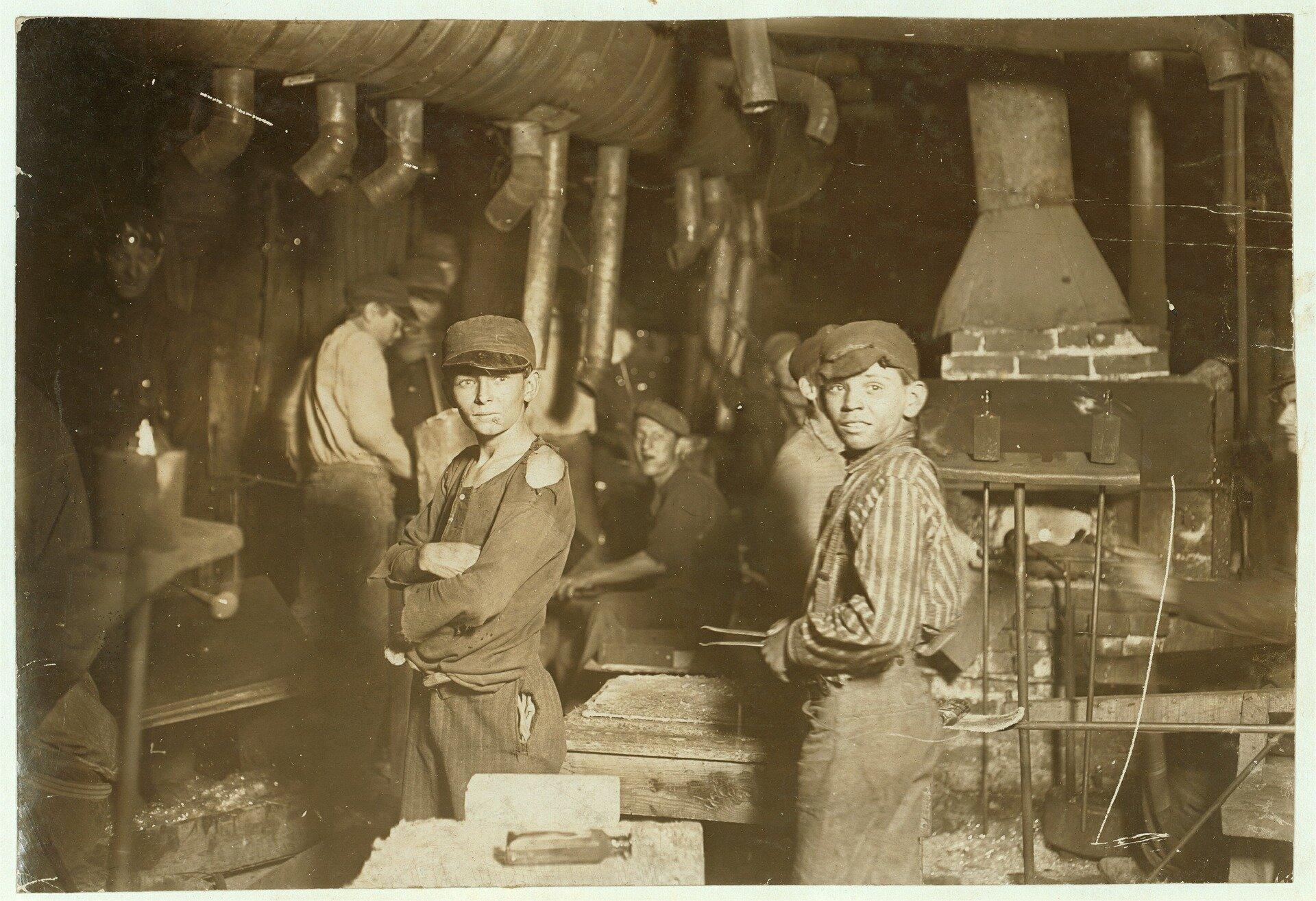 archiwalne zdjęcie przedstawia halę zmaszynami, whali znajdują się dzieci wpodartych izniszczonychstrojach, znarzędziami wrękach
