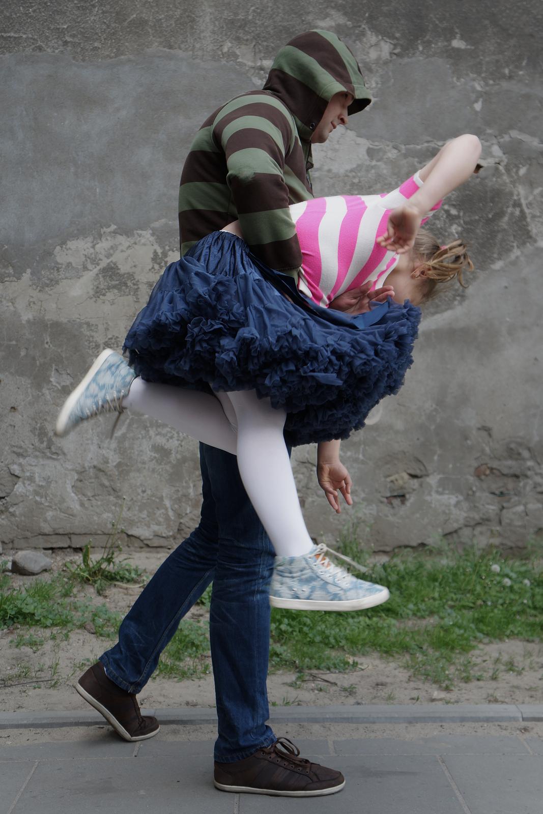 Zdjęcie przedstawia mężczyznę niosącego dziewczynkę. Mężczyzna ubrany wsweter zkapturem na głowie. Mężczyzna trzyma dziewczynkę prawą ręką na wysokości pasa. Zawieszona na wysokości pasa, głowa dziewczynki skierowana wprawą stronę zdjęcia, nogi po lewej stronie. Dziewczynka próbuje się wyrwać, wymachuje rękami inogami. Mężczyzna idzie wprawą stronę.