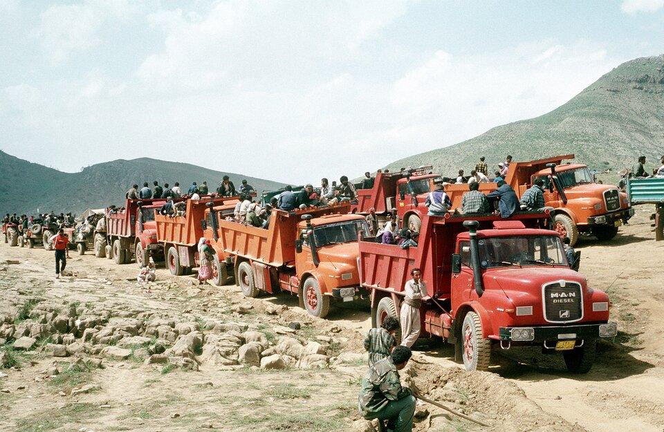 Konwój czerwonych wielkich ciężarówek – wywrotek. Wszystkie pełne ludzi. Wokół teren górzysty prawie pozbawiony roślinności. Niebo błękitne, białe obłoki, słonecznie.