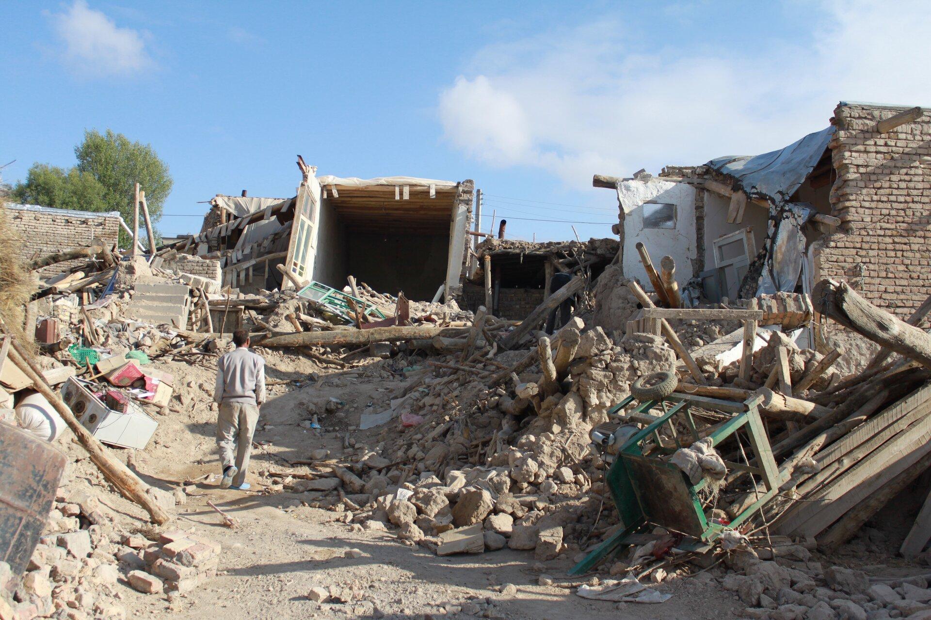 Na zdjęciu zburzone domy, na ulicy sterty gruzu idrewna.