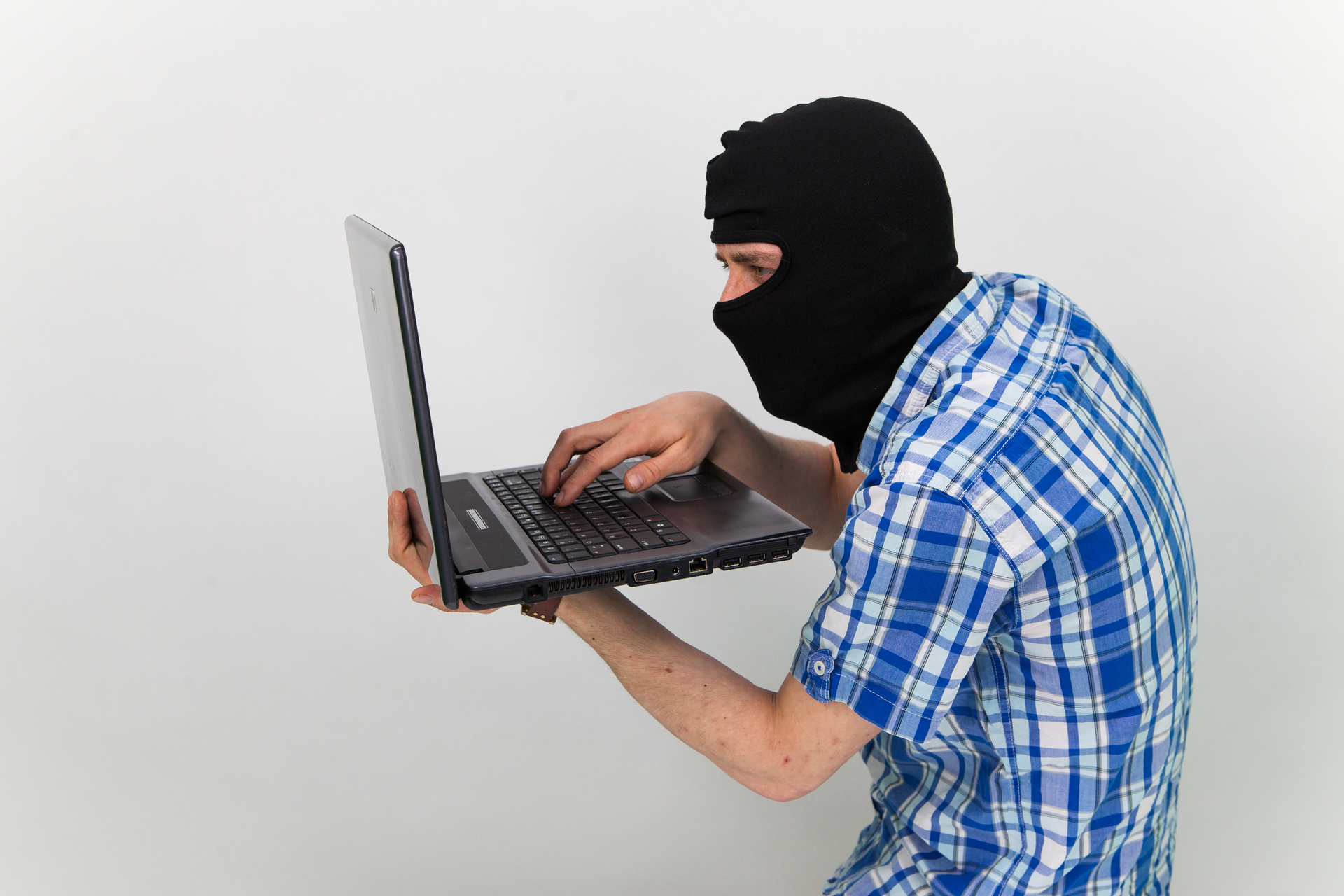 Zdjęcie przedstawia mężczyznę wczarnej kominiarce na głowie. Mężczyzna stoi bokiem do obserwatora zdjęcia. Skierowany wlewo. Zamaskowany mężczyzna trzyma otwarty laptop wlewej ręce. Prawą ręką pisze na klawiaturze.
