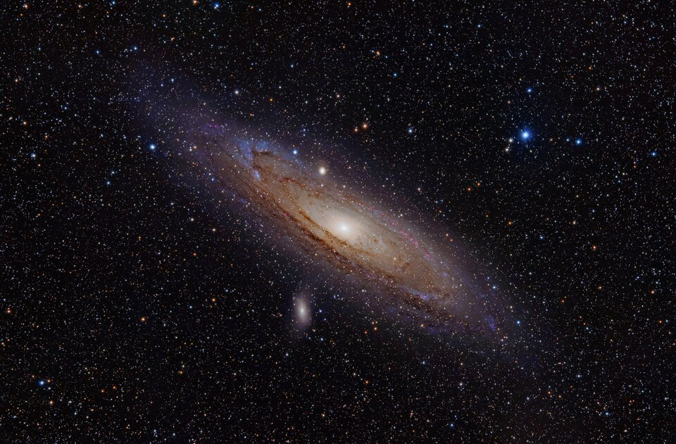 Zdjęcie przedstawia obraz galaktyki spiralnej przechylonej pod kątem około 30 stopni do poziomu na tle innych ciał niebieskich. Ma ona postać dysku zbardzo intensywnie jasnym obszarem wsamym środku ikoncentrycznymi ciemniejszymi kręgami dookoła.