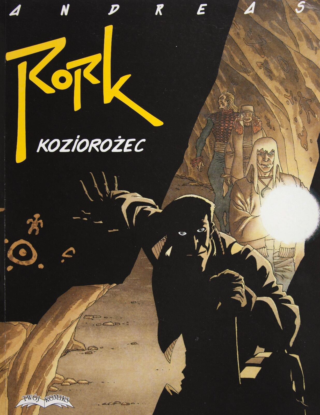 """Ilustracja przedstawia okładkę do komiksu Andreasa """"Rork. Koziorożec"""". Ukazuje grupę osób przemierzających podziemny korytarz jaskini. Postać na pierwszym planie ukryta jest wciemności. Światło pada na mężczyznę ztyłu, rozświetlając jedynie fragmenty ubrania itwarzy. Prawą ręką daje znak do zatrzymania się osób idących za nim. Przestrzeń wtle jest oświetlona lampą przez jedną ztrzech idących dalej osób. Trzy te postacie idą jedna za drugą. Mężczyzna na końcu rozgląda się. Lewa strona okładki jest czarną, zaciemnioną częścią skały. Znajdują się na niej namalowane znaki, apowyżej zostały zamieszczone: nazwisko autora itytuł komiksu."""