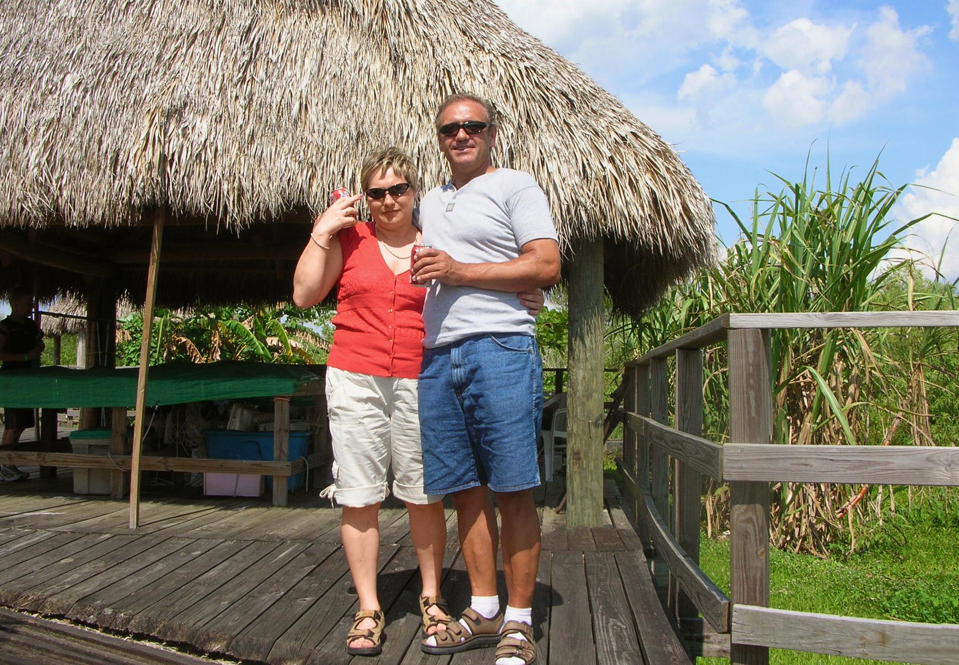 Fotografia przedstawia parę ludzi wwieku około 50 lat. Stoją da drewnianym tarasie, za nimi trzcinowe zadaszenie. Są objęci iuśmiechnięci.