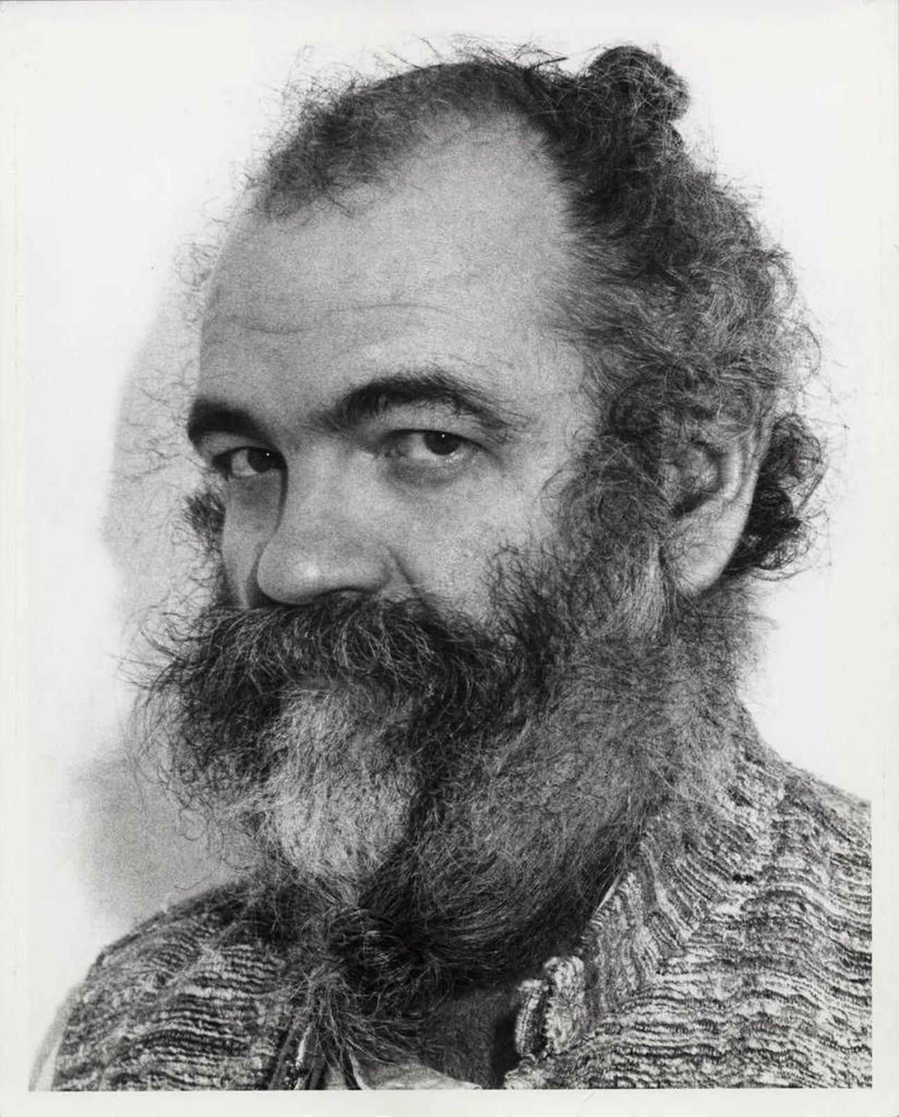 Ilustracja przedstawia fotografię La Monte Younga. Ukazany jest ekscentryczny mężczyzna zzarośniętą brodą. Kompozytor ubrany jest wszary sweter. Ma zawiązane dwie kitki: jedną na czubku głowy, drugą zrobioną na brodzie.