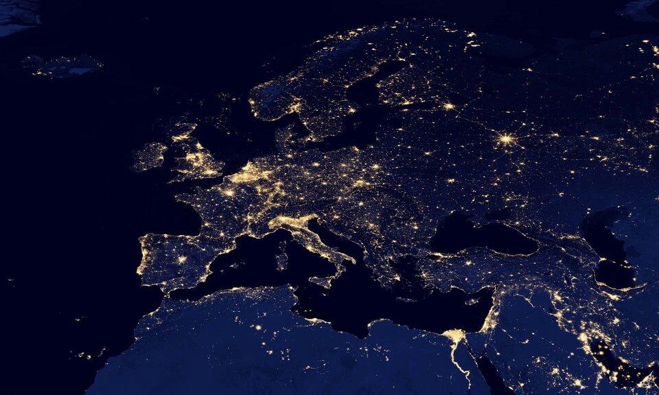 Zdjęcie satelitarne Europy nocą. Na zdjęciu widać zarys kontynentu. Widoczne są światła wielkich aglomeracji. Światła to żółte punkty na tle granatowej Europy. Duże skupiska świateł tworzą żółte plamy. Najbardziej oświetlone są północne Włochy, Niemcy oraz Wyspy Brytyjskie. Pojedyncze punkty to mniejsze miasta.
