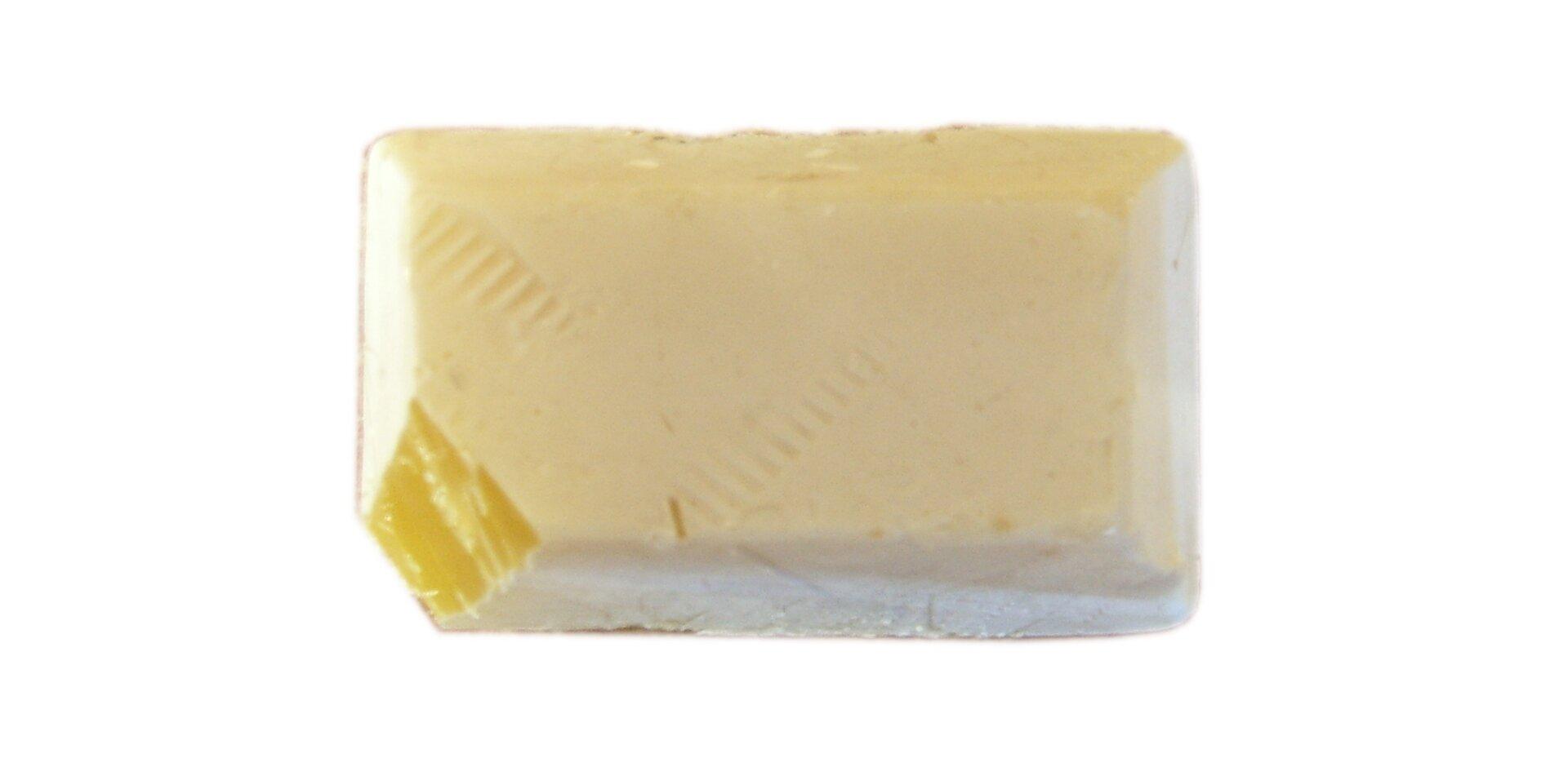 Zdjęcie przedstawia fosfor biały wpostaci kremowej kostki zobciętym narożnikiem, przez który widać intensywnie żółte zabarwienie wnętrza kawałka.