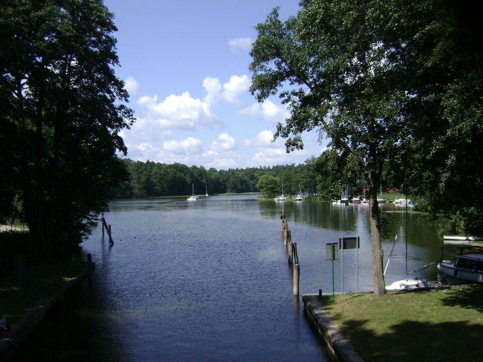 Na zdjęciu jezioro zprzystanią. Na drugim brzegu las.