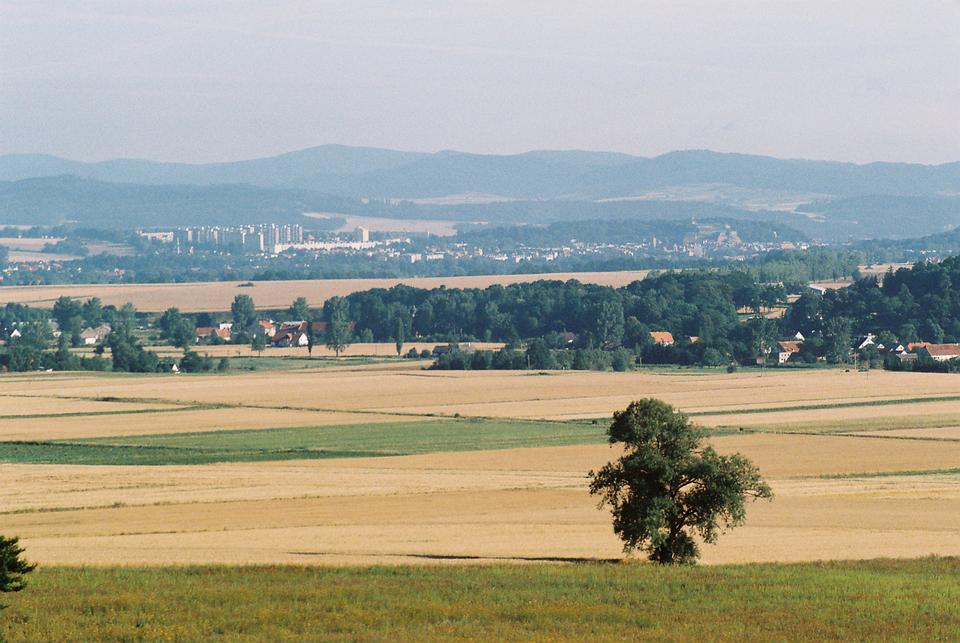 Fotografia ukazująca teren równinny zpolami iłąkami, wtle widoczne wzniesienia otaczające teren.