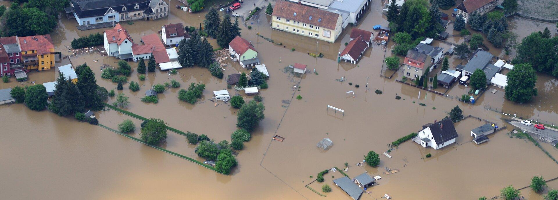 Kolorowe zdjęcie niewielkiej miejscowości zrobione zgóry. Cały obszar zalany jest wodą. Zwody, która jest wkolorze brązowym, wystają pojedyncze domy jednorodzinne, budynki, drzewa isamochody.