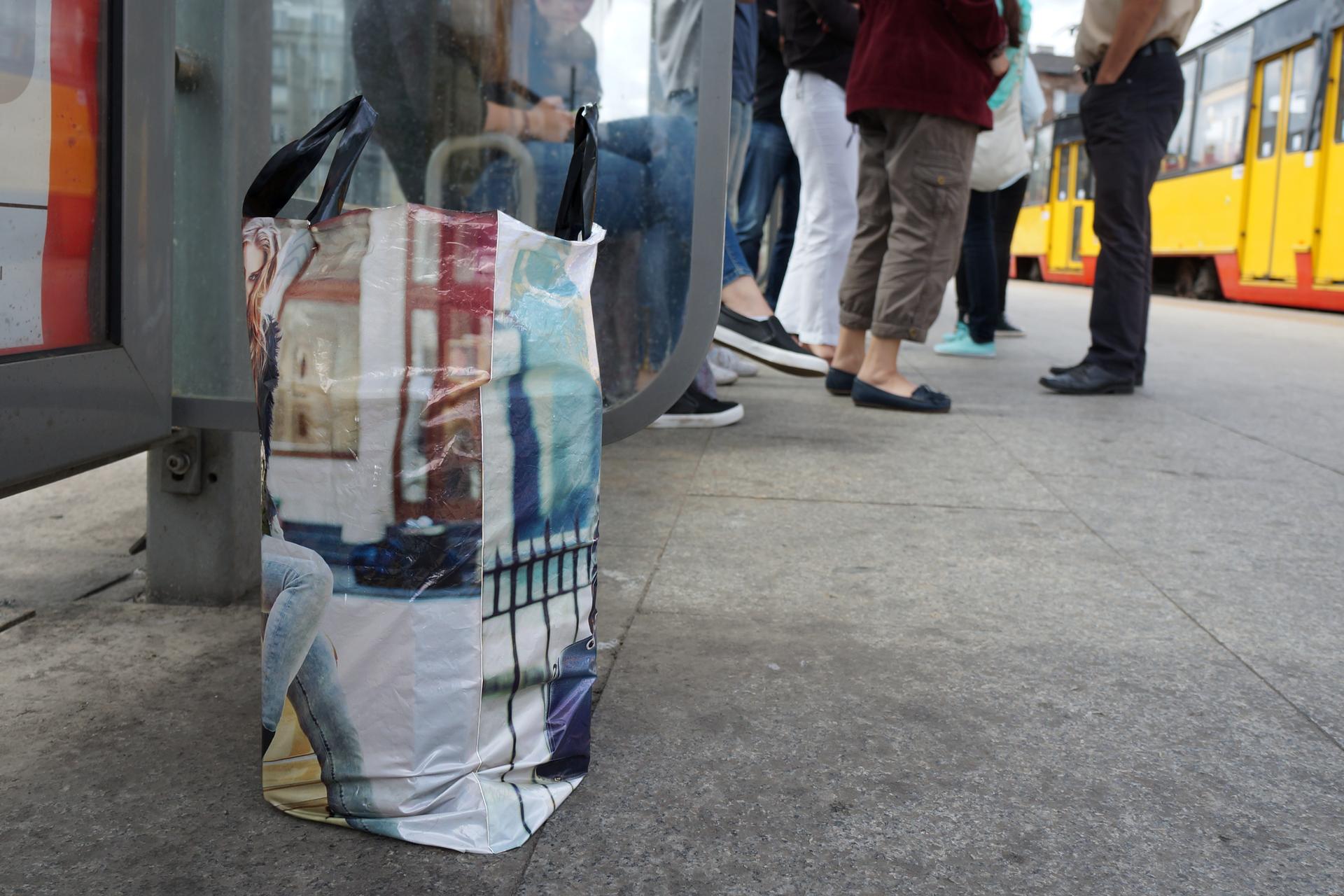 Zdjęcie przedstawia pozostawioną reklamówkę na przystanku tramwajowym. Reklamówka zawiera nieznaną zawartość. Wgłębi zdjęcia czekający pasażerowie. Po prawej stronie zdjęcia żółto-czerwony tramwaj.