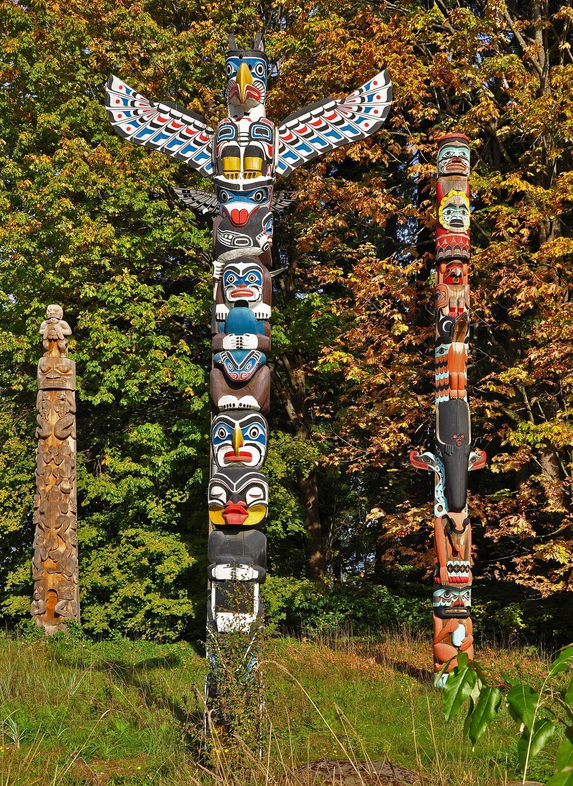 Ilustracja przedstawia wysoki drewniany słup, który jest ozdobiony kolorowymi, zdobionymi twarzami, które są ułożone kolejno od spodu. Na samym szczycie znajdują się orle skrzydła, nad którym ukazana jest pomalowany głowa orła. Wtle znajdują się dwa kolejne totemy (zdobione wpodobny sposób).