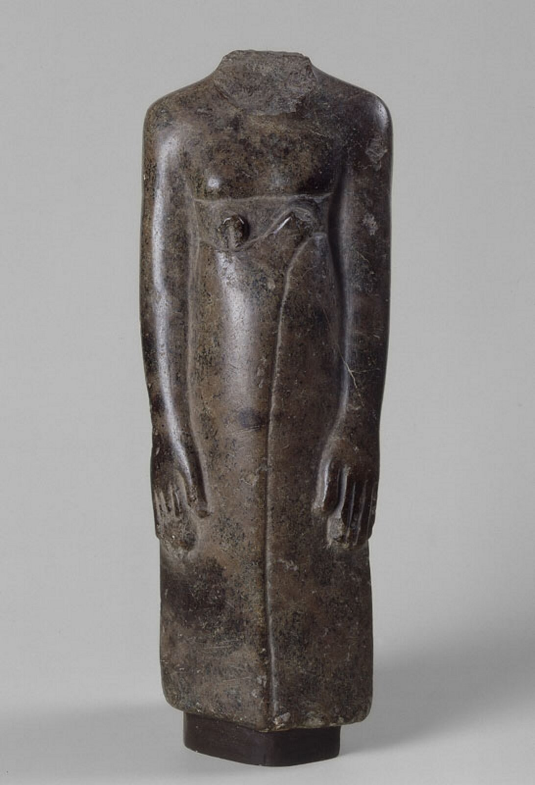 """Ilustracja przedstawia rzeźbę """"Fragment figurki mężczyzny - kapłana"""". Widoczna jest stojąca sylwetka postaci bez głowy. Rzeźba wykonana jest prawdopodobnie zdiorytu. Ręce są ułożone wzdłuż tułowia."""