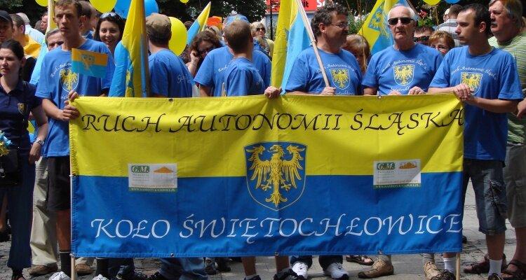 Zdjęcie przedstawia grupę mężczyzn trzymających żółto-niebieski transparent znapisem: Ruch Autonomii Śląska. Koło Świętochłowice.