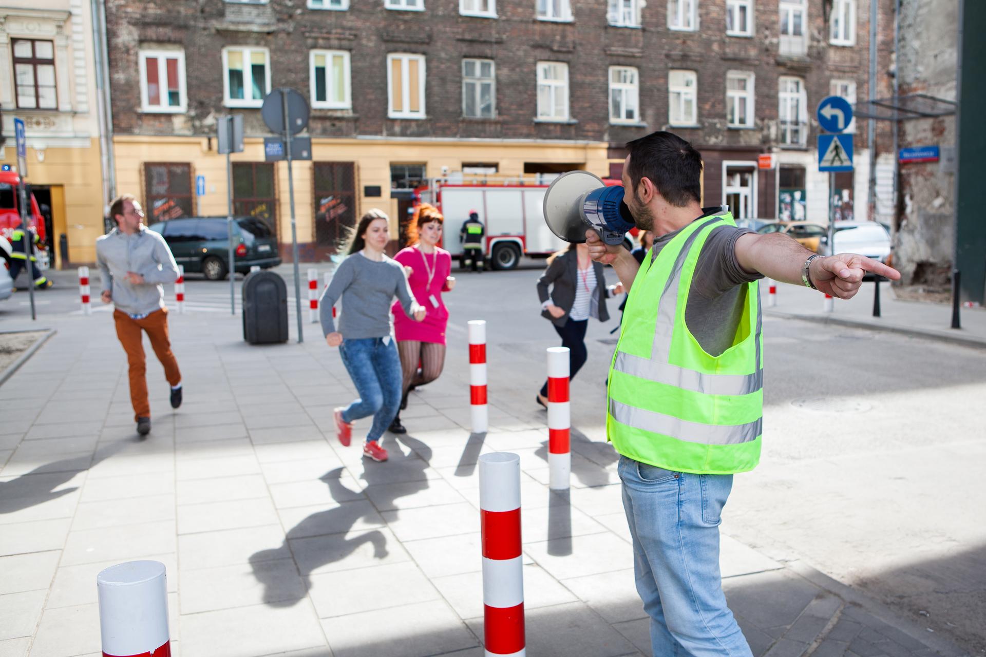 Zdjęcie przedstawiające kierownika ewakuacji wraz zmegafonem, który instruuje ludzi gdzie mają się ewakuować. Grupa młodych ludzi biegnie wkierunku wskazywanym przez niego ręką. Wtle widać fragment ulicy ipas kamienic oraz stojący na jezdni wóz strażacki.