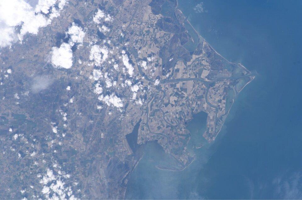 Na zdjęciu satelitarnym delta rzeki wpostaci kilku odnóg, tworzących obszar okształcie przypomi-nającym grecką literę Δ (delta). Tereny rolnicze. Zprawej strony morze, jasny pas materiału niesione-go przez rzekę.