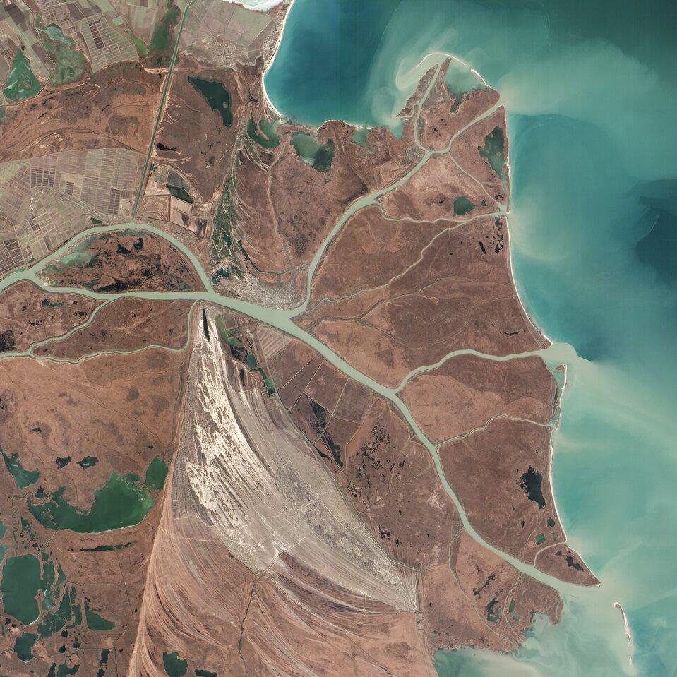 Na zdjęciu satelitarnym delta rzeki wpostaci kilku odnóg, tworzących obszar okształcie przypomi-nającym grecką literę Δ (delta). Tereny pomiędzy kolejnymi odnogami pozbawione roślinności. Zprawej strony turkusowe morze, jasne smugi materiału niesionego przez rzekę.