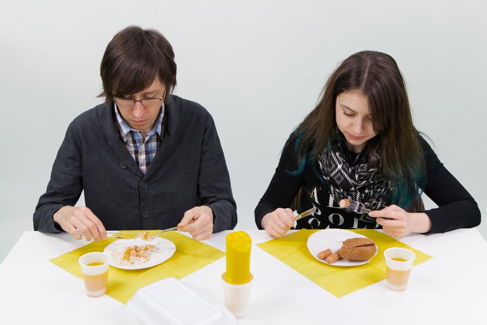 Fotografia przedstawia dwójkę młodych ludzi spożywających posiłek, podany na jednorazowych naczyniach.