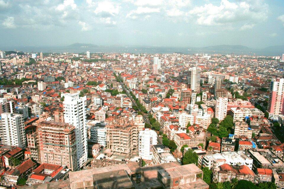 Na zdjęciu zwarta zabudowa wdużym mieście. Przewaga białych budynków zczerwonymi dachami. Wtle góry.