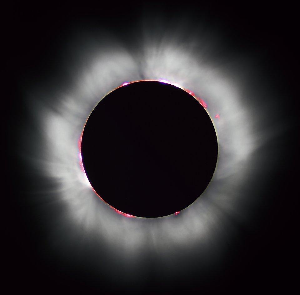 Fotografia ukazuje zaćmienie Słońca. Tarcza słoneczna jest zakryta na czarno, na obwodzie zakrytego Słońca biała promienista poświata.