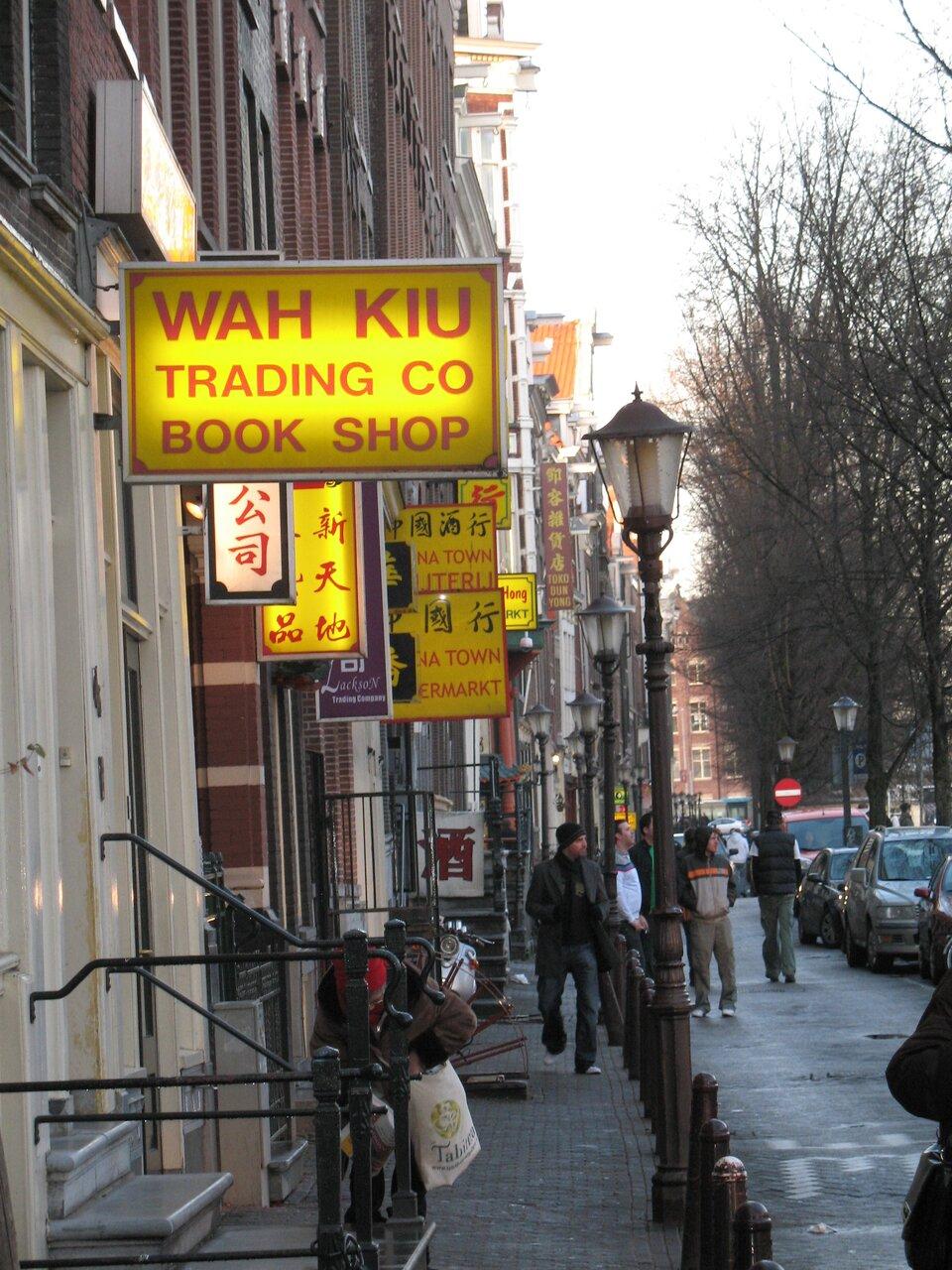 Ulica wchińskiej dzielnicy wAmsterdamie, na budynkach duża ilość żółtych neonów zczerwonymi chińskimi napisami.