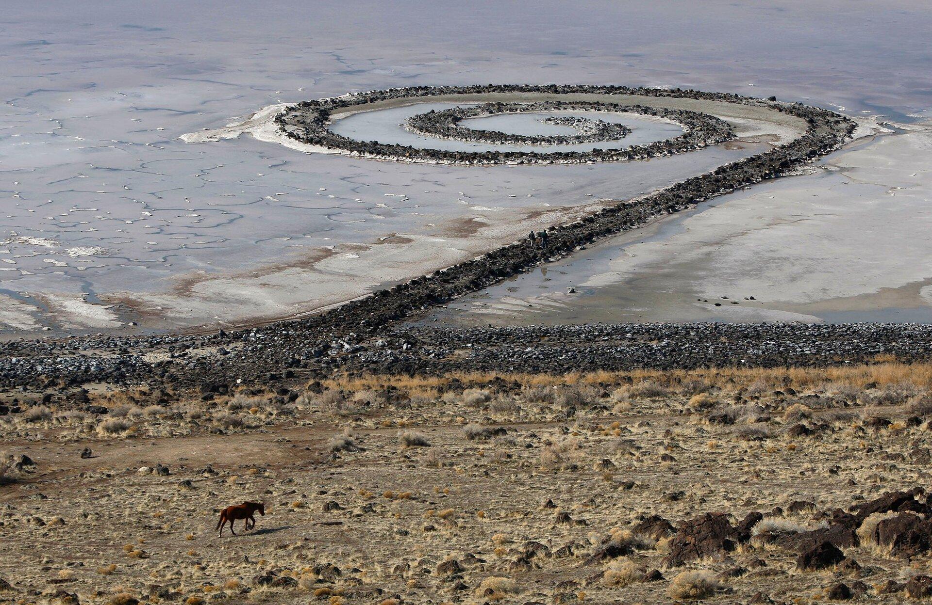 Ilustracja przedstawia utworzoną zkamieni ipiachu wizję artystyczną przypominającą kształtem muszlę ślimaka. Artysta wykorzystał 6 tysięcy ton ziemi ikamienia, zktórych usypał 500 metrową spiralną groblę. Realizacja trwała 6 dni. Wwyniku działania czynników atmosferycznych pierwotny wygląd grobli nieodwracalnie się zmienił.