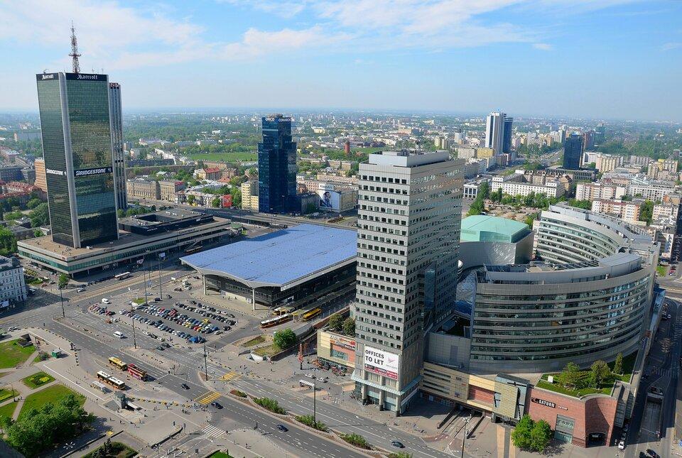 Na zdjęciu nowoczesna zabudowa usługowa ibiurowa. Wysokie budynki, dworzec, parkingi.