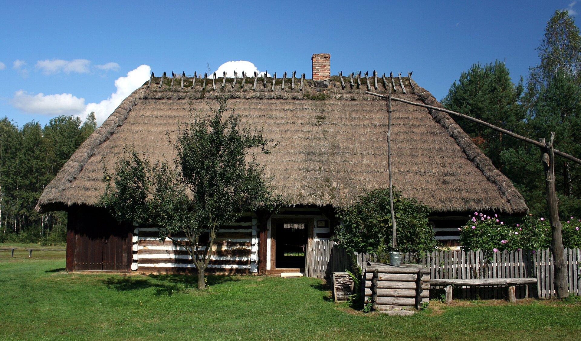 Fotografia prezentuje drewniany dom pokryty strzechą, typowy dla tradycyjnego budownictwa polskiego.
