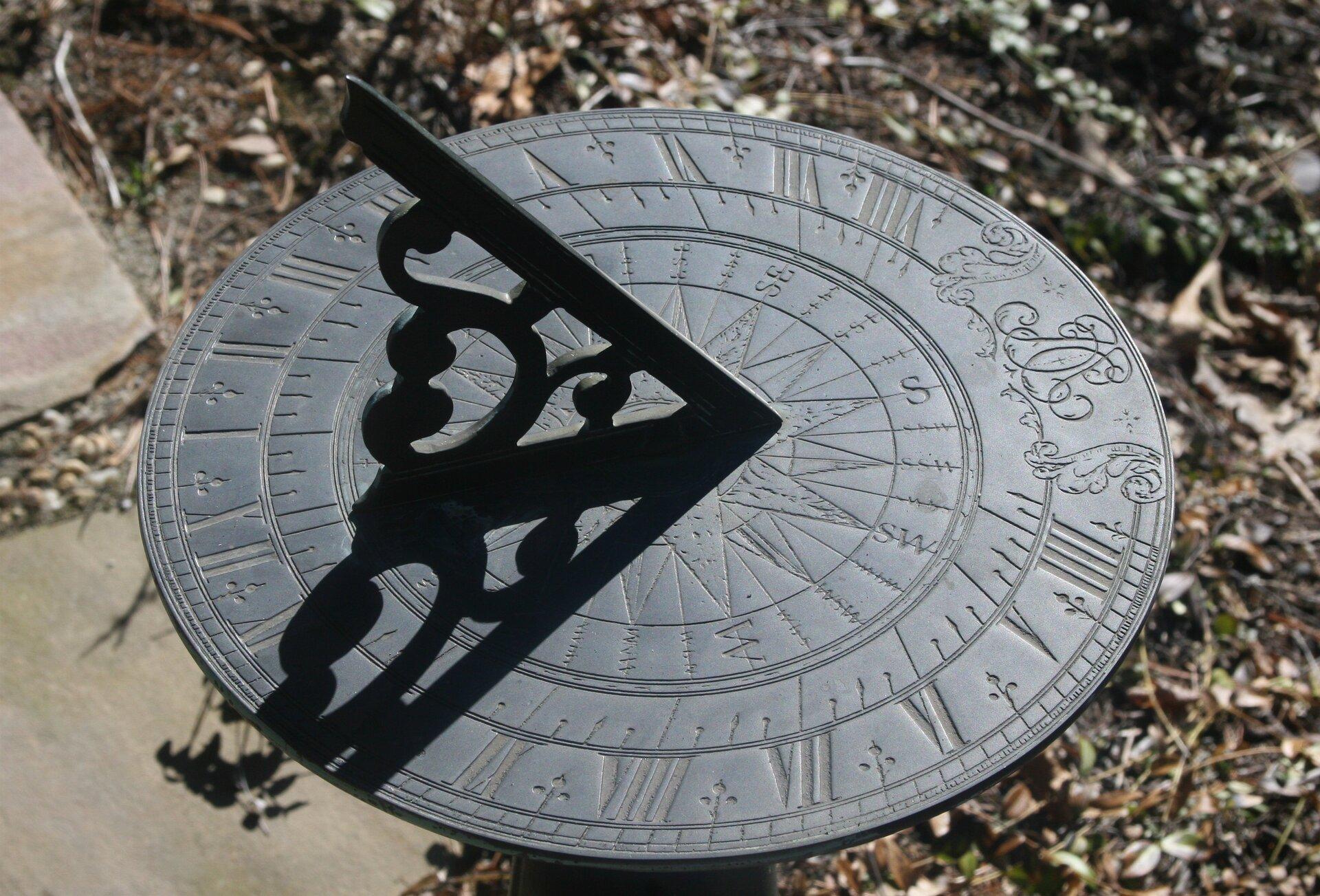 Fotografia prezentuje okrągłą metalową tarczę zegara słonecznego zwyrytymi rzymskimi cyframi od 1 do 12 na obrzeżach tarczy. Wśrodku tarczy znajdują się ramiona róży kierunków świata. Do tarczy przymocowana jest prostopadle trójkątna wskazówka, której cień pokrywa cyfrę 10.