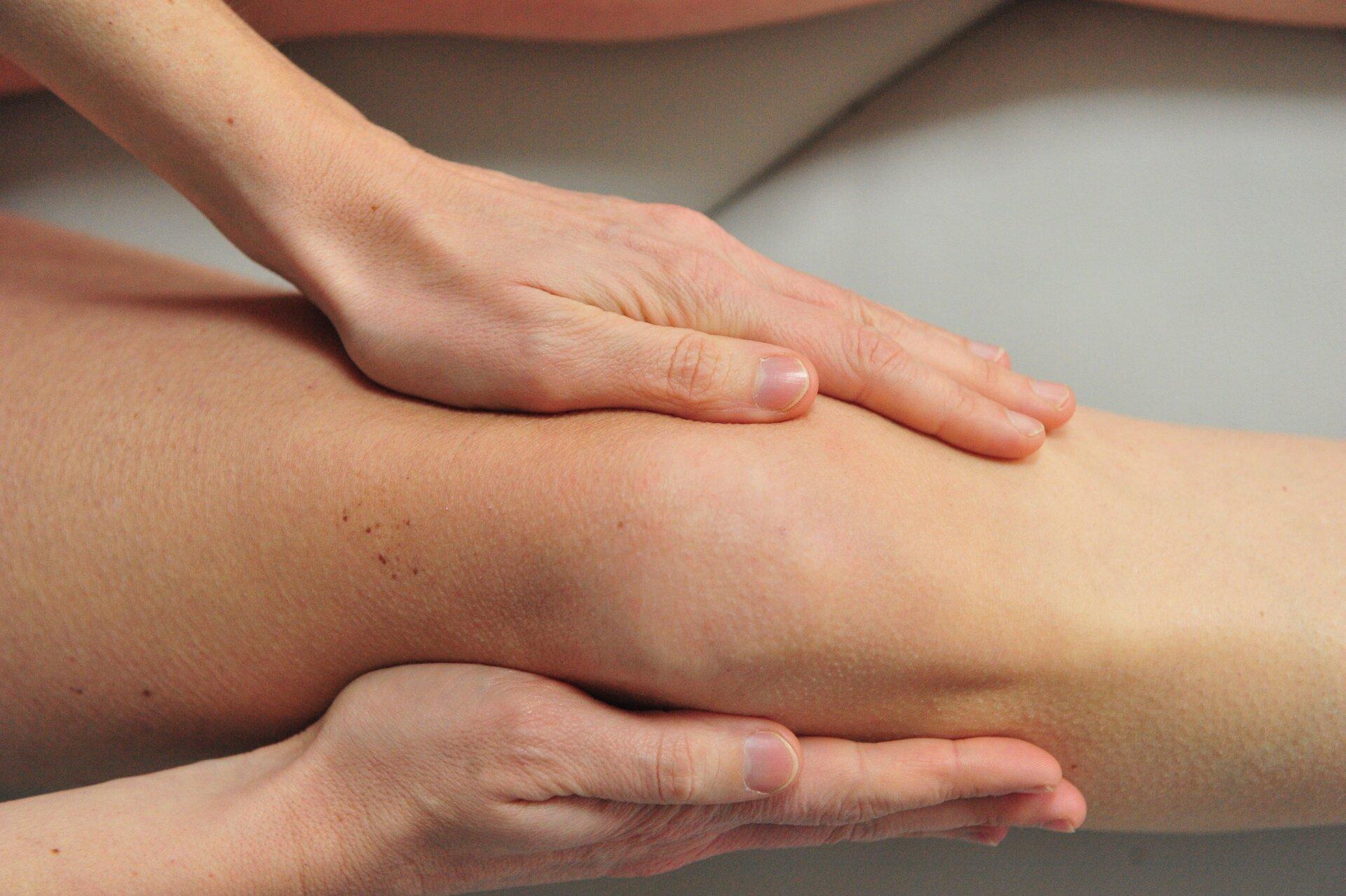 Fotografia przedstawia poziomo nogę człowieka, na wysokości kolana objętą dłońmi osoby, wykonującej masaż. Taki masaż usprawnia krążenie limfy.
