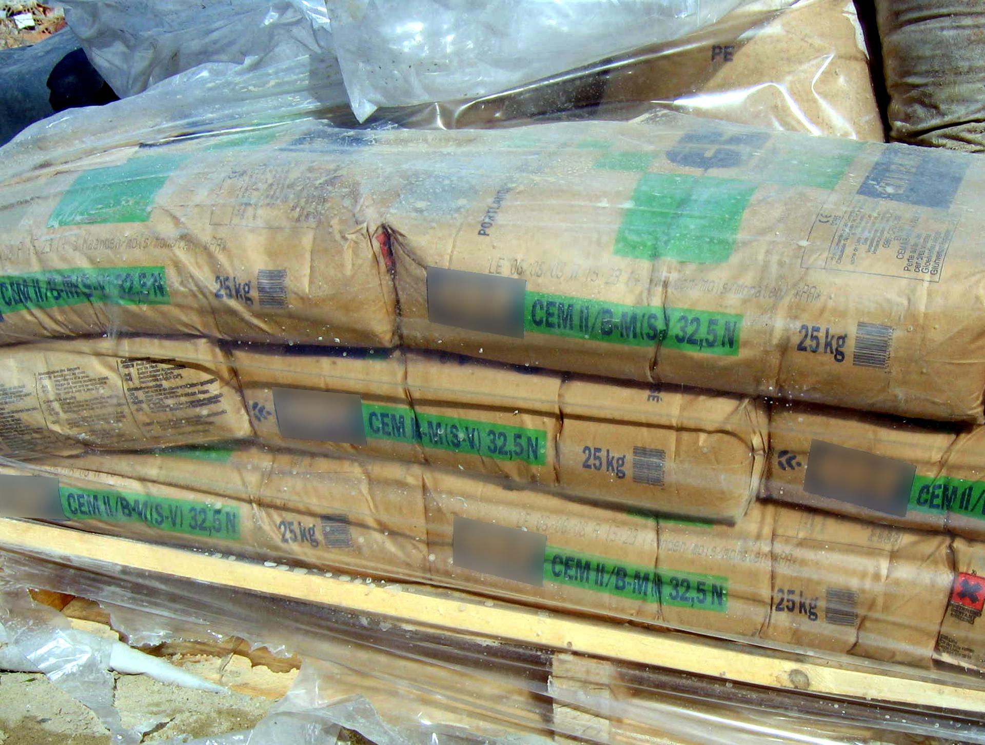 Zdjęcie przedstawia dwudziestopięciokilogramowe worki cementu ułożone na palecie transportowej iściągnięte grubą folią. Marka producenta została wymagana zobrazka.