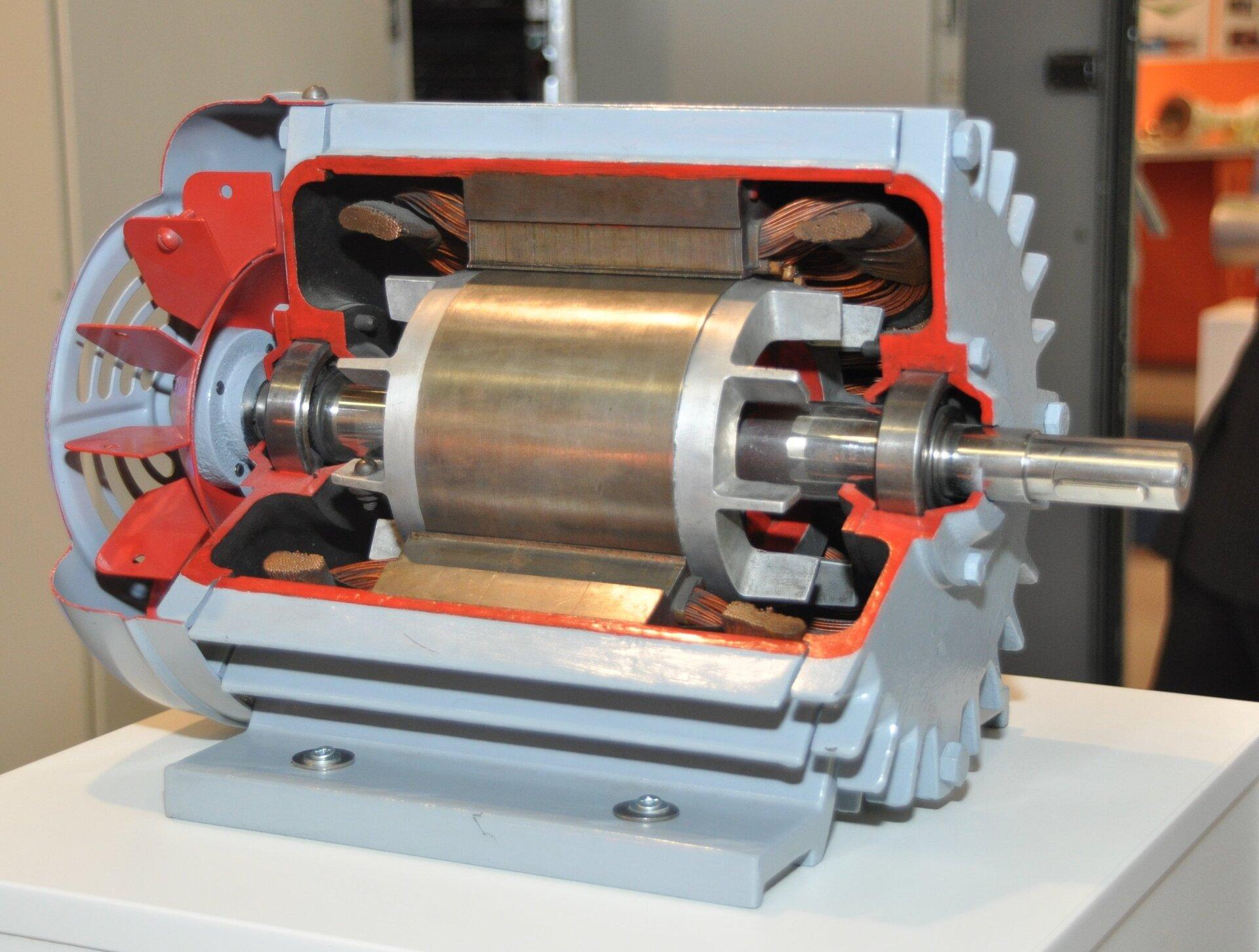 Zdjęcie przedstawia przekrój pokazowy silnik elektryczny. zwyciętą mniej więcej jedną trzecią korpusu celem ukazania budowy wewnętrznej urządzenia. Wcentralnej części znajduje się wirnik, czyli część obrotowa. Ma ona postać długiego wału do którego przymocowany jest metalowy nieregularny cylinder otoczony blachą pełniącą rolę komutatora. Komutator ugóry iudołu przekroju styka się zmetalowymi szczotkami, do których podłączona jest wiązka kabli elektrycznych. Zewnętrzna część korpusu silnika pomalowana jest na kolor srebrny, natomiast część wewnętrzną wyróżniono kolorem czerwonym.