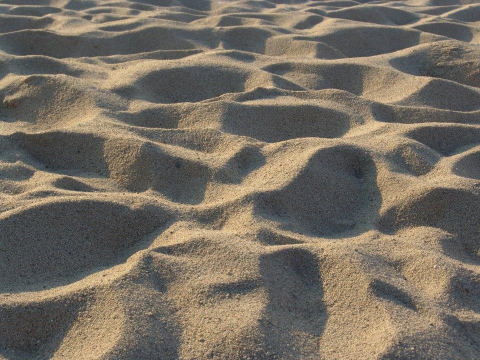 Druga fotografia prezentuje sypki piasek.