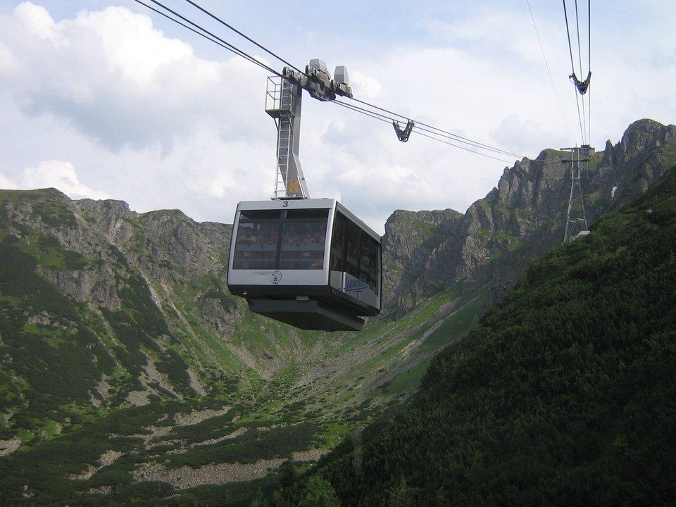 Fotografia prezentuje jadący wagonik linowej kolejki górskiej. Wtle widoczna panorama gór wysokich.