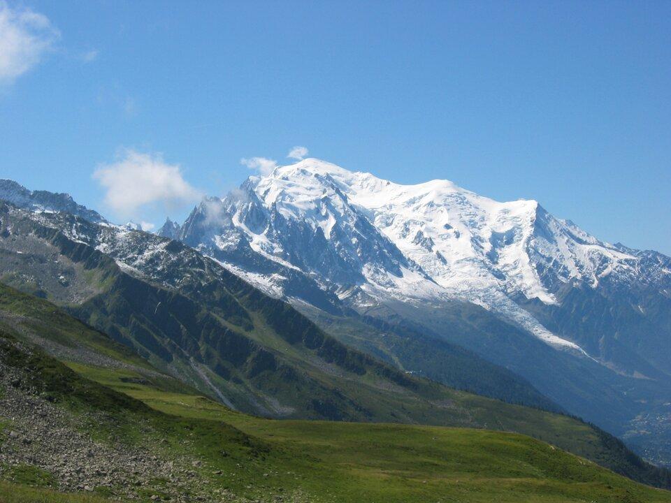 Na zdjęciu wysokie, skaliste, ośnieżone góry, na pierwszym planie rozległa górska polana porośnięta trawą.