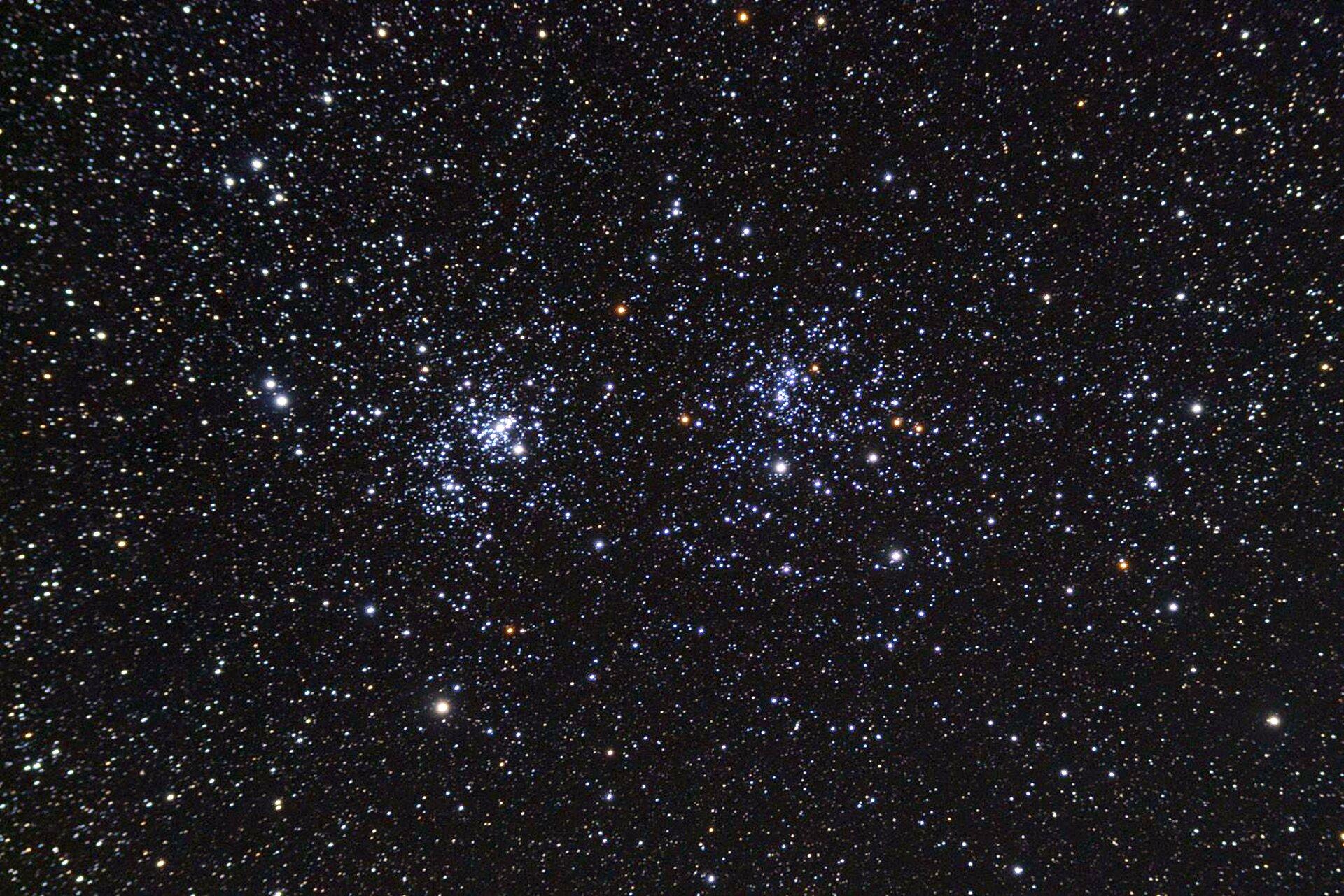Grafika przedstawia podwójną gromadę gwiazd wgwiazdozbiorze Perseusza. Tło czarne. Na grafice widoczne mnóstwo białych, jasnożółtych, jasnopomarańczowych, jasnozielonych ijasnobłękitnych drobnych punktów. Wypełniają całą grafikę. Na środku widoczne dwa duże skupiska punktów.