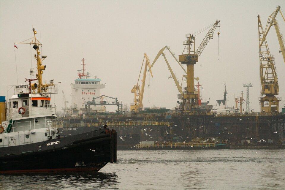 Na zdjęciu urządzenia idźwigi portowe, statki.