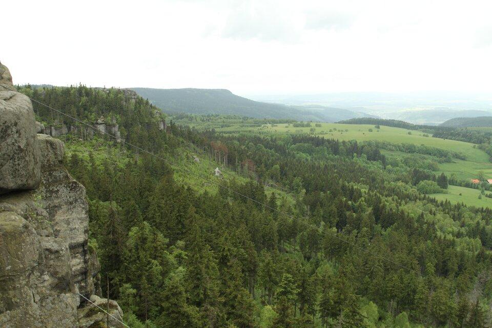 Na zdjęciu pasma górskie zpłaskimi grzbietami porośnięte lasem mieszanym. Pomiędzy drzewami strome skałki.