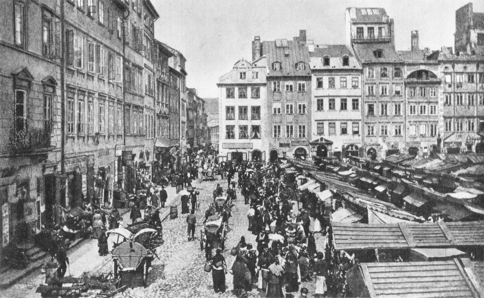 Ilustracja przedstawia rynek Starego Miasta wWarszawie. Jest to kwadratowy plac otoczony kamieniczkami. Na środku placu znajdują się liczne drobne stragany. Po rynku spaceruje bardzo dużo ludzi, jeżdżą również furmanki zaprzężone wkonie.