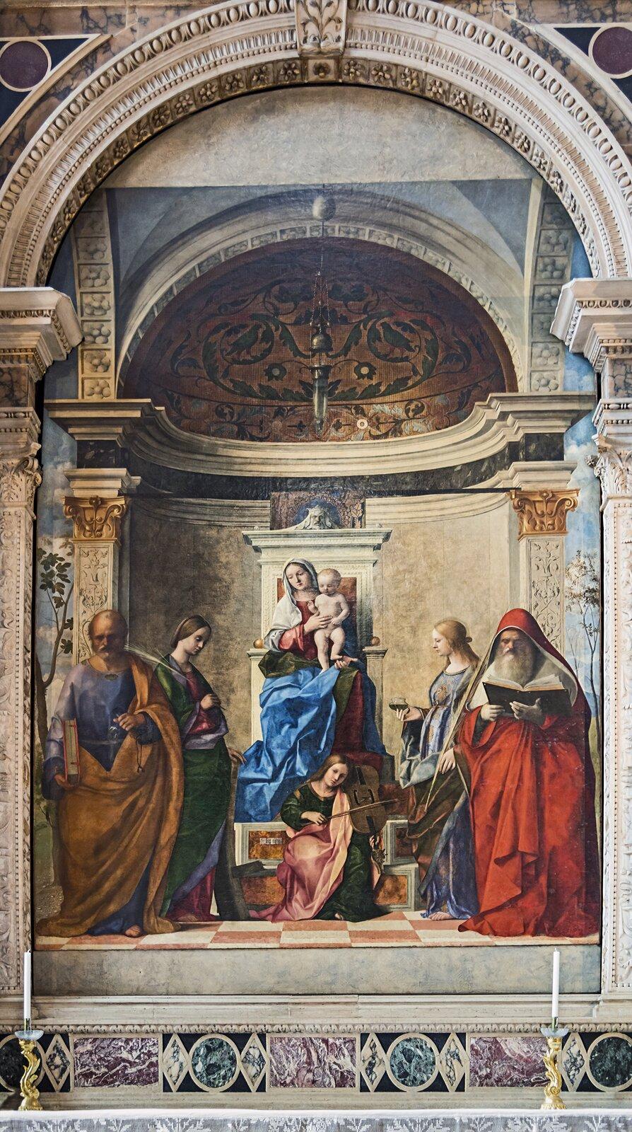 """Ilustracja okształcie pionowego prostokąta przedstawia obraz Giovanniego Belliniego """"Tronująca Maria zDzieciątkiem iświętymi"""". Ukazuje grupę osób we wnętrzu, usytuowanych wniszy. Wcentrum znajduje się Madonna zDzieciątkiem siedząca na tronie wotoczeniu świętych ianioła. Kompozycja jest symetryczna. Wnękę niszy dekorują korynckie pilastry ze złoconymi głowicami, zwieńczone ozdobnym łukiem. Wgłębi niszy znajduje się półkopuła dekorowana malowidłami."""