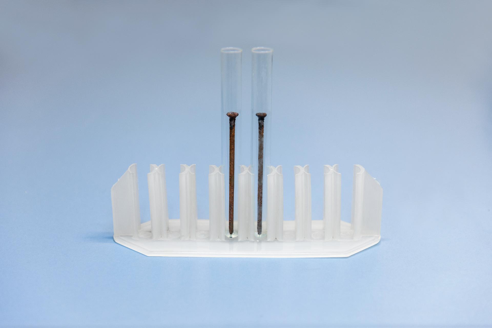 Piąte zdjęcie wgalerii przedstawia plastikowy stojak na probówki zdwiema małymi probówkami, wktórych nie ma żadnych płynów, ale są dwa duże gwoździe. Gwóźdź zlewej strony jest zardzewiały. Gwóźdź po prawej stronie ma ślady rdzy, ale znacznie mniejsze. Redukcja stopnia zardzewienia to efekt kilkudniowej kąpieli wkwasie fosforowym.