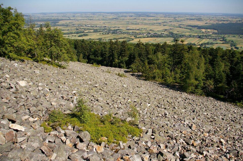 Na zdjęciu stok górski pokryty ostrymi kamieniami. Wdole rozległy teren równinny.