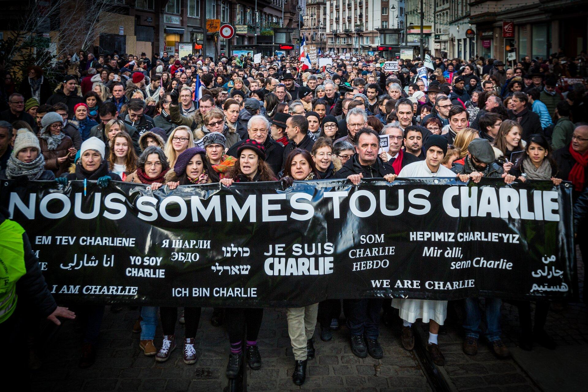 """Na zdjęciu tłum ludzi na ulicach miasta. Na pierwszym planie czarny transparent zbiałymi napisami wróżnych językach """"Jestem Charlie""""."""