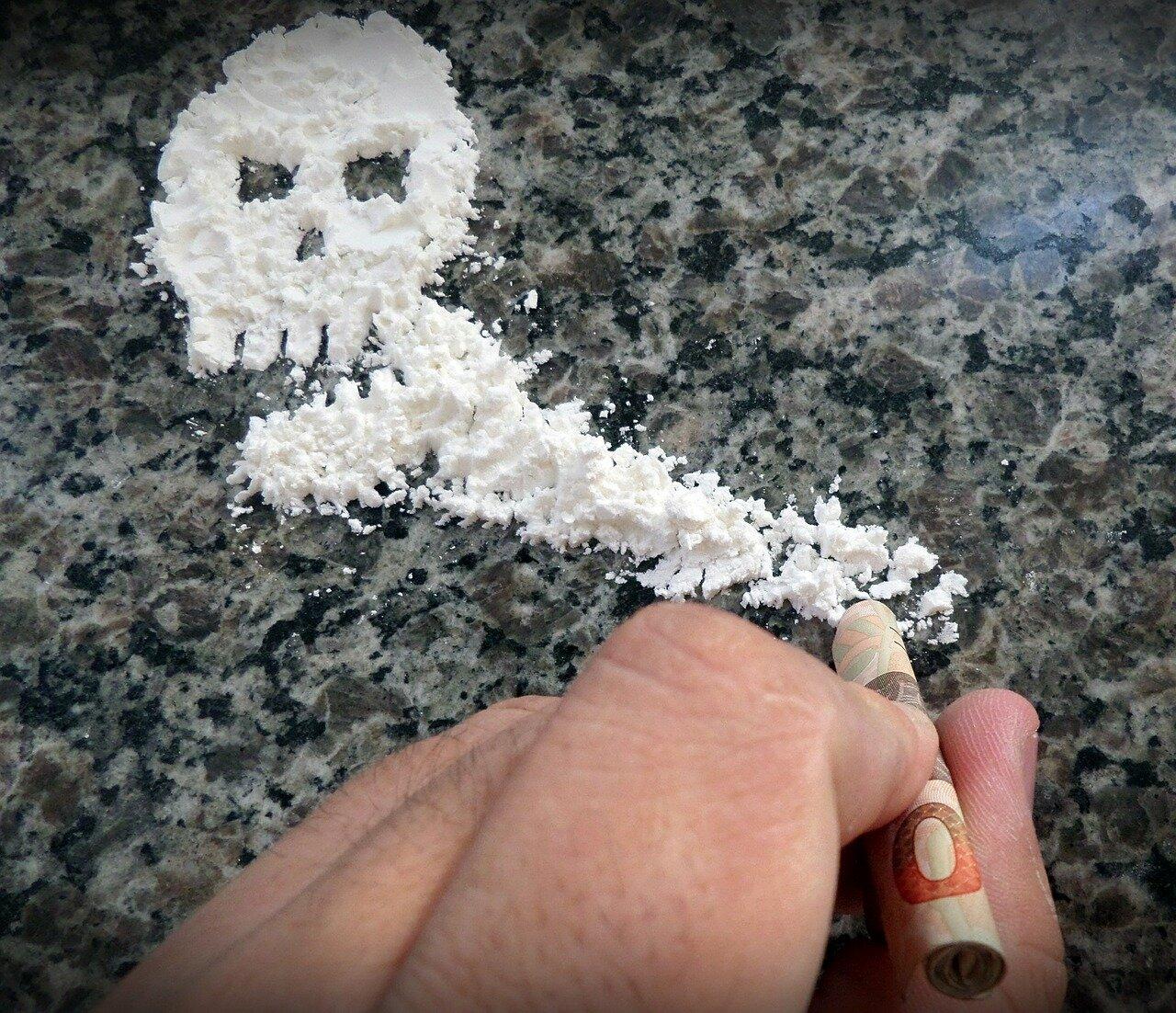 na zdjęciu widac biały proszek tworzacy kształt trupiej czaszki, zboku widać ręke człowieka ze zwniętym banknotem