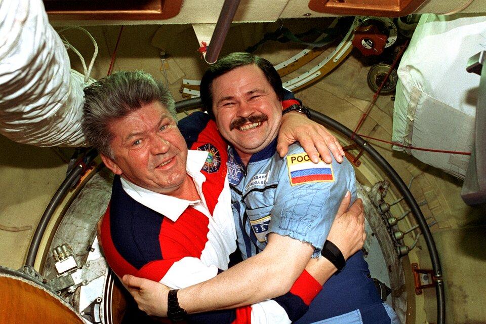 Zdjęcie przedstawia dwóch kosmonautów na stacji Mir. Mężczyźni wwieku ok. 50 lat. Obejmują się ipozują do zdjęcia. Mężczyzna po lewej ma siwiejące włosy, ogorzałą twarz oraz widoczne zmarszczki. Oczy jasne. Nos duży. Ubrany wkoszulkę polo zdługim rękawem wgranatowo-czerwono-białe pasy zbiałym kołnierzykiem. Mężczyzna po prawej ma krótkie, ciemne włosy, starannie zaczesane zprzedziałkiem po prawej stronie (jego lewej). Mężczyzna szeroko się uśmiecha pokazując zęby. Oczy zmrużone. Mężczyzna ma ciemne wąsy. Ubrany jest wniebieski kombinezon znaszytą na lewym ramieniu flagą Rosji. Obaj mężczyźni noszą czarne zegarki.