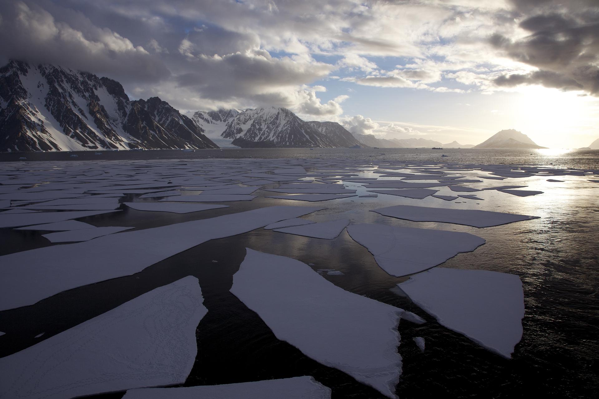 Fotografia prezentuje krajobraz Antarktydy latem. Na pierwszym planie widoczna kra pływająca po morzu. Wtle góry pokryte częściowo śniegiem, nad nimi kłębiaste chmury oraz słońce nad horyzontem.