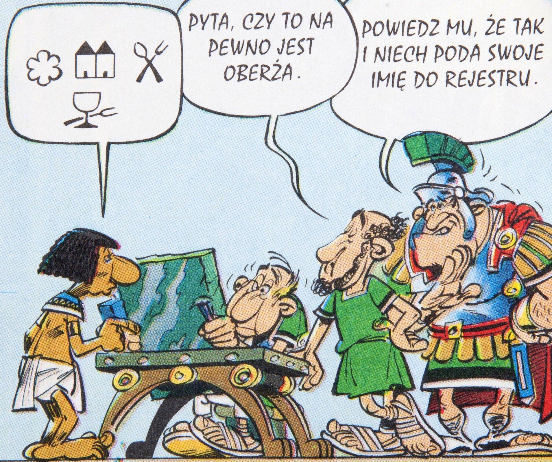 """Ilustracja przedstawia fragment komiksu """"Asterix legionista"""". Ukazuje grupę osób. Po lewej stronie Egipcjanin, używając skomplikowanego kodu językowego, różnego od tego, którym posługują się inni rozmówcy, dyktuje tekst zapisywany dłutem na tablicy przez skrybę, siedzącego przy stoliku. Wdymku znajdują się znaki ikoniczne: kwiatek, dwie wieże, łyżka iwidelec oraz kieliszek iwidelec. Mężczyzna tłumaczy Rzymianinowi: """"Pyta, czy to na pewno jest oberża"""", na co wojownik odpowiada: """"Powiedz mu, że tak iniech poda swoje imię do rejestru""""."""