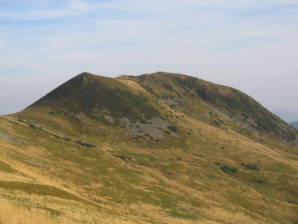 Na zdjęciu wąski, ostry, nieco wydłużony grzbiet góry, zdwoma wyraźnymi wierzchołkami, na stokach złomiska skał.